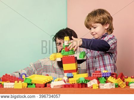 Dad And Kid Build Plastic Blocks. Child Care Development And Upbringing. Father Son Game. Father And