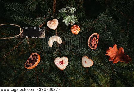 Ginger Biscuits, Cookies And Other Cakes And Christmas Decoration On Dark Coniferous Background - So
