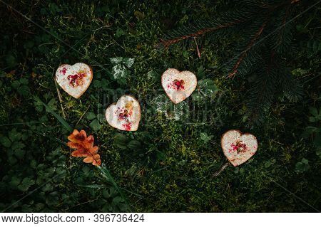 Photo Of Illuminated Heart Biscuits (cakes) Covered Of Sugar Laying On The Green And Frozen Grass -