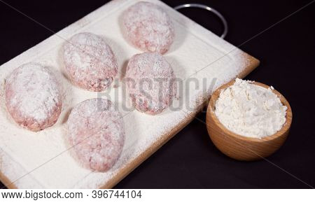 Semi-finished Products-homemade Minced Meat Cutlets, Sprinkled With Flour On A Wooden Board. Close-u