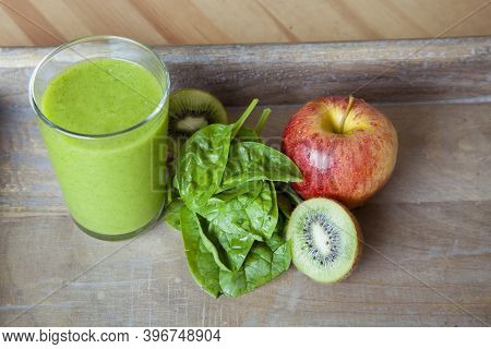 Top View Of Green Smoothie Made From Vegetables, Fruits And Green Leaves On Wooden Tray