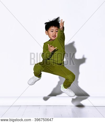 Faceless Dark-haired Boy Jumping Against The Background Of A White Wall In The Studio. The Child Is