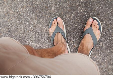 Top View On Strong Male Legs And Feet In Flip Flops. Healthy Nails And Skin. Concept Of Health And H