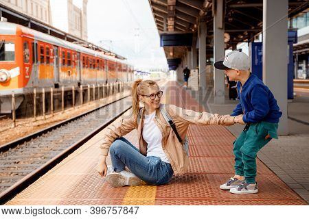 Woman With Son On The Platform Near The Train. Girl With A Preschool Boy Sitting At The Train Statio