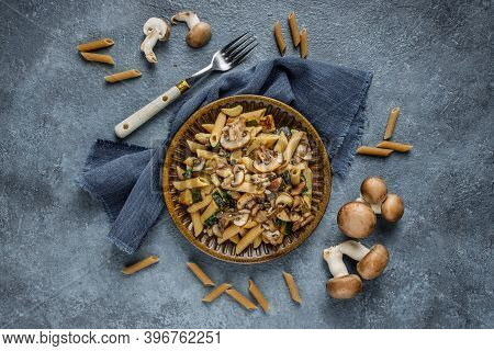 Flat Lay Photo Of Pasta Penne With Roasted Mushrooms, Garlic And Zucchini. Italian Food On Blue Marb