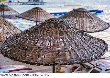 Wicker roof beach umbrella on blue sea background