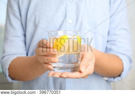Woman Holding Glass Of Soda Water With Lemon Slices And Ice Cubes, Closeup