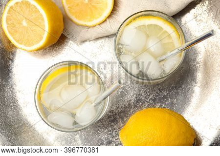 Soda Water With Lemon Slices And Ice Cubes On Silver Tray, Flat Lay
