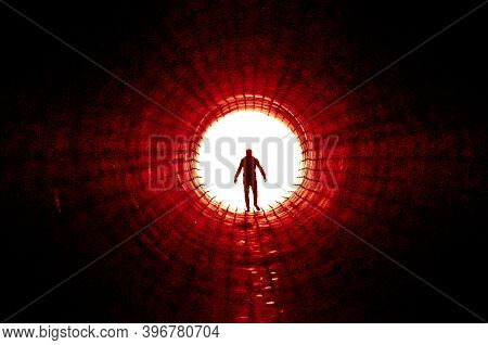 Silhouette Of A Man Walking To The Light At The End Of A Big Tunnel. Concept Of Escape, Exit, Freedo