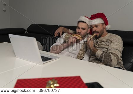 Young Caucasian Gay Couple With Santa Claus Hats Watching Movies On The Laptop And Eating Pizza On T