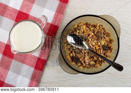 Glass Pitcher With Yogurt On Checkered Napkin, Baked Muesli, Teaspoon In Transparent Brown Bowl On W