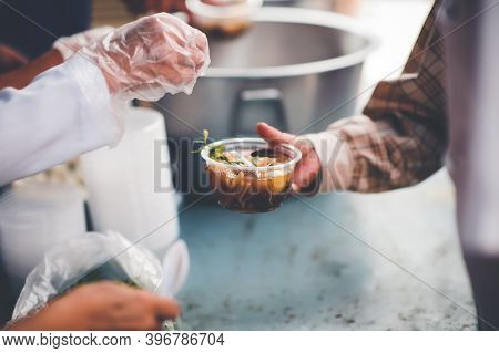 Concept Of Charity Food For The Poor: Volunteers Give Food To The Poor