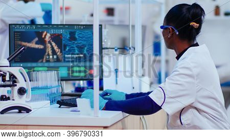 African Woman Biochemist Researcher Checking Manifestations Of Vaccine Working In Modern Equipped La