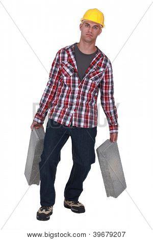 Mason carrying cinderblocks