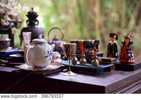 Teapot And Decorative Wine Glass In Focus On The Foreground, Tea Ceremony In The East, Clay Teapot A