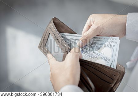 Young Man Took Out The 100 Dollar Bill From The Brown Purse, Spending Money With Cash, Campaign To U