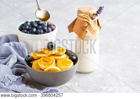 Mini Pancakes In A Bowl With Maple Syrup. Dutch Mini Pancakes Are Called Strawberry Potato Pancakes.
