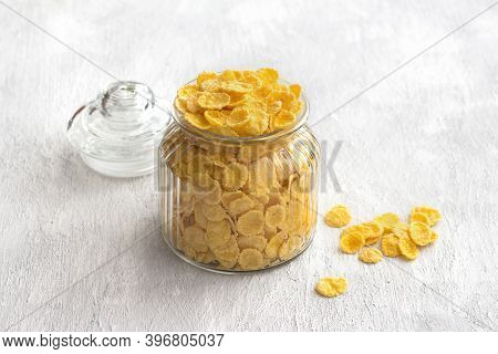 Sweet Crunchy Cornflakes In A Glass Jar On A Gray Textured Background. Fast Tasty Breakfast, Free Sp