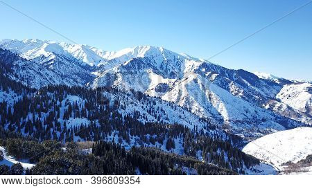 Winter Forest High In The Mountains. Top View From The Throne Of The Snowy Mountains And Hills. Fir