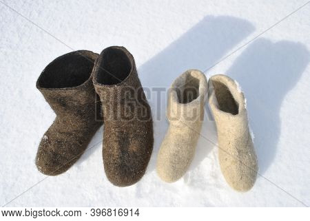 Two Pairs Of Boots Stand In The Snow. Boots Top View. White And Brown Shoes. Valenoks Are Covered Wi