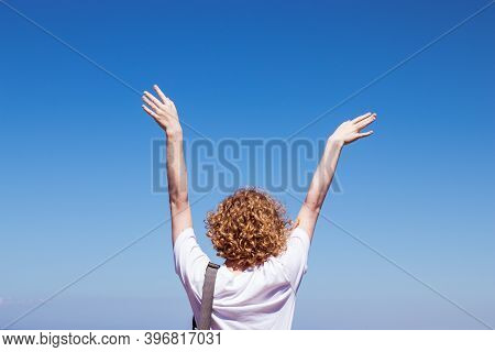 Woman Raised Her Hands To The Blue Sky With Copy Space. Girl Feeling Happy To Travel, Joy Of Freedom