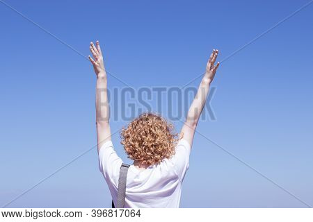 Young Female European Tourist Back View, Raised Hand, Curly Blond Hair. Sky Copy Space.