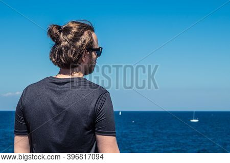 Guy With Long Hair Looking At Blue Sea. Tourism Concept, Freelancer And Copy Space