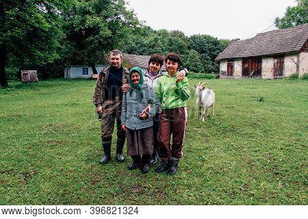 Hutir, Volyn / Ukraine - May 27 2013: Ukrainian Family Posing In Front Of Old House In Farmstead