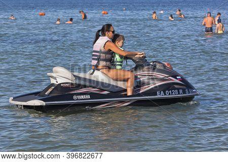 Zaozyornoye, Evpatoria, Crimea, Russia - July 23, 2020: Mom And Child Go To Ride A Jet Ski Near The