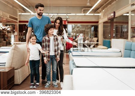 Happy Family Buys New Orthopedic Mattress In Furniture Store. Blissful Family Choosing Mattresses In