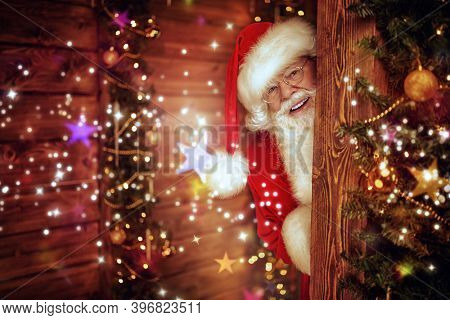 Cheerful Santa Claus looks into a wooden house, beautifully decorated for Christmas. Festive lights flicker around.