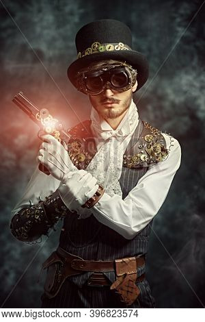 Portrait of a courageous victorian steampunk man standing with a gun on a grunge background. Fantasy world, adventures.