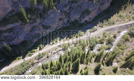 Top View Of The Cave, Forest, Rocks And Road. A Group Of Tourists Walking Along The Trail. There Is