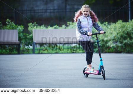 Smiling Little Girl Rides Scooter In Park. Empty Space For Text