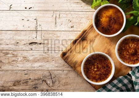 Homemade Creme Brulee In Bowl On Wooden Table.top View. Copy Space