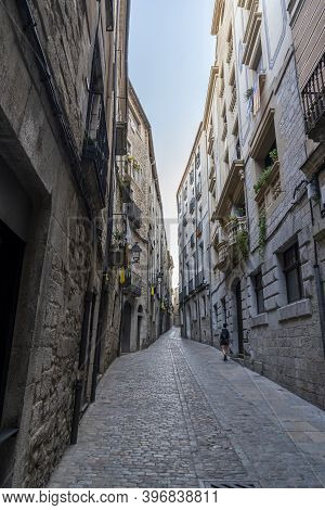 Views Of The Narrow Streets Of The Old Town Of Girona With A Woman.