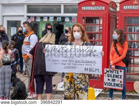 Richmond, North Yorkshire, Uk - June 14, 2020: A Young Girl Wearing A Face Mask Holds A Banner About