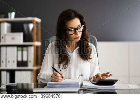 Professional Accountant Calculating Sale Tax Invoice At Desk
