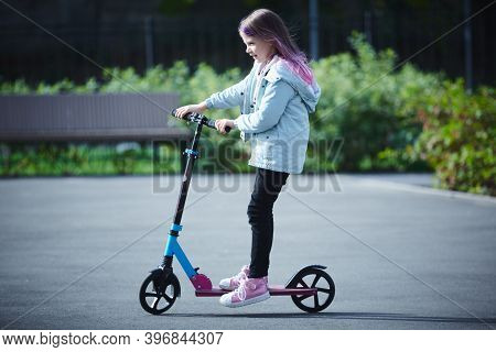 Happy Beautiful Girl Is Riding Along The Street On The Kick Scooter On A Windy Day. Baby Having Free