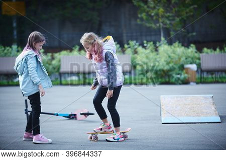 Little Girl In The Park Learns To Ride A Skateboard.