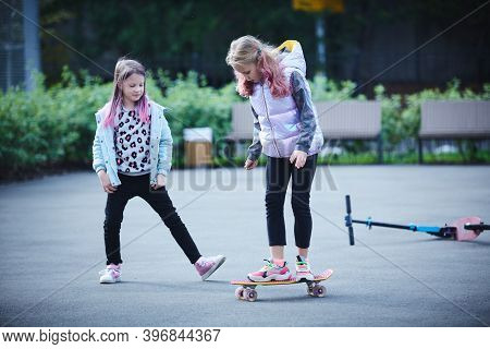 Two Pretty Little Sisters Having Fun Together Learning To Skateboard Outdoors. The Concept Of A Heal