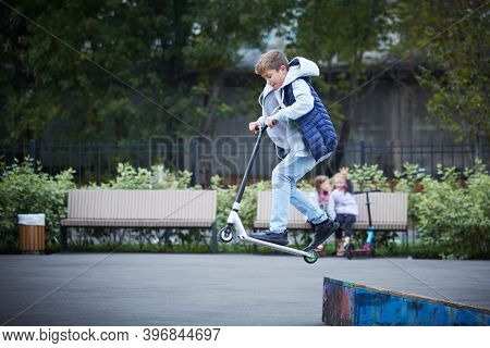 Boy Jumps With His Scooter At The Skate Park. The Concept Of A Healthy Lifestyle. Kids Sport.