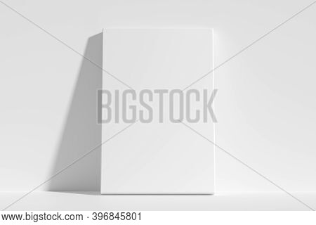 Blank White Empty Vertical Rectangular Poster On Floor Leaning At Empty White Wall, White Bleached C