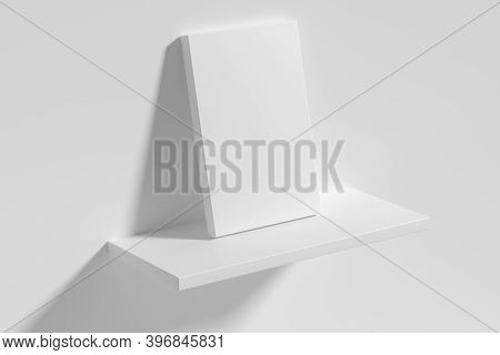 Blank White Empty Rectangular Poster On White Shelf Leaning At Empty White Wall, Top Diagonal View,