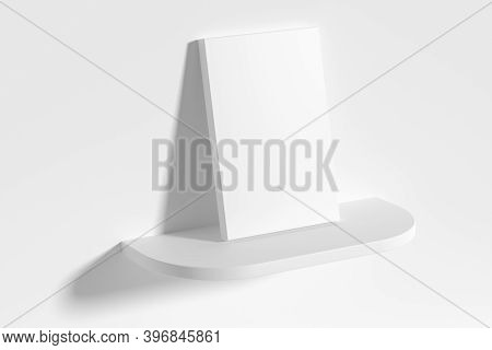 Blank White Empty Rectangular Poster On White Rounded Shelf Leaning At Empty White Wall, Top Diagona