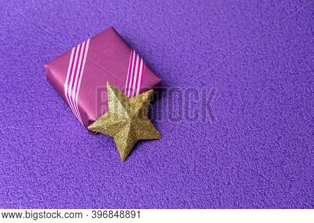 Gift In Violet Packaging, Next To The New Years Star On A Violet Background. Free Space For Entering