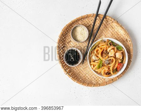 Udon Noodles With Seafood And Vegetables Cooked In A Wok In A White Bowl On A Wicker Tray. Top View.