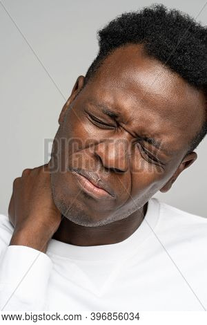 Frustrated Black Man Holding Hand On His Neck, Closed Eyes, Suffers From Pain And Pinched Nerve In F