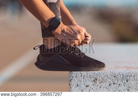 Close Up Of Slim Caucasian Woman Runner Tying Shoelaces. Preparing For A Run. Fitness, Wellness, Hea