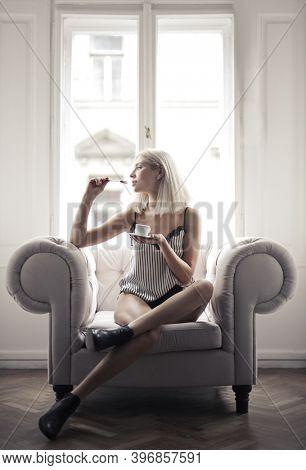 beautiful woman sitting on an armchair drinks a coffee